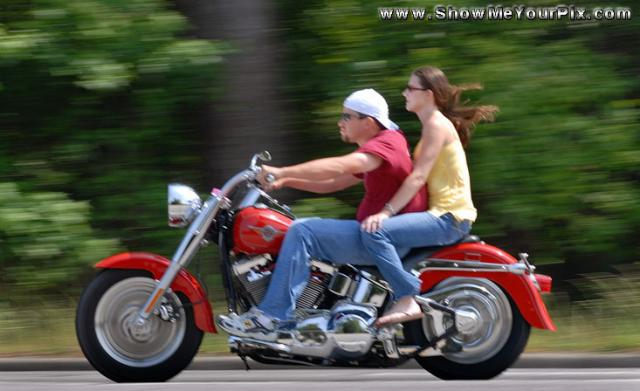 A couple ride along North Kings Highway on their red Harley.