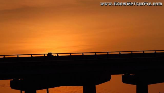 A couple ride into the sunset over Route 9 and the Intercoastal Waterway, North Myrtle Beach.